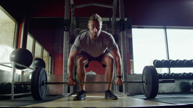vidéos et rushes de slow motion shot of an attractive caucasian man in his twenties performing deadlifts with a barbell while weightlifting at a gym - entraînement aux haltères