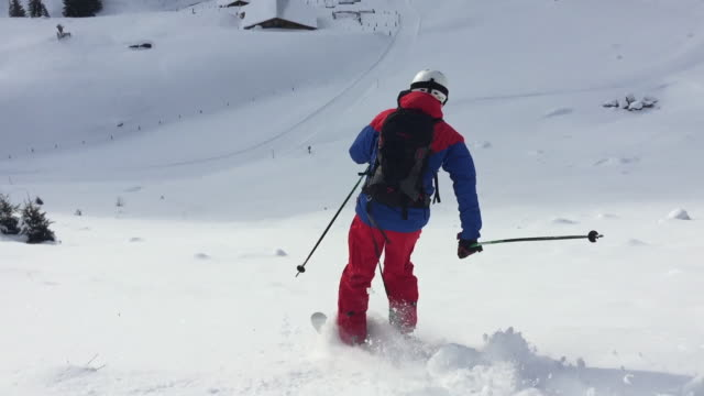 Slow Motion shot of an extreme backcountry skier skiing down the hill through deep snow. Powder.