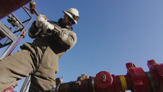 slow motion shot of an oilfield worker in his thirties pumping down lines and hitting a pipe with a hammer at an oil and gas drilling pad site on a cold, sunny, winter morning - hammer stock videos & royalty-free footage
