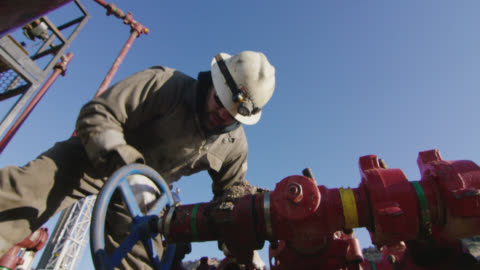 slow motion shot of an oilfield worker in his thirties pumping down lines at an oil and gas drilling pad site on a cold, sunny, winter morning - petrol stock videos & royalty-free footage