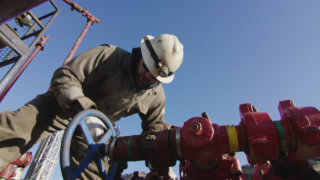 slow motion shot of an oilfield worker in his thirties pumping down lines at an oil and gas drilling pad site on a cold, sunny, winter morning - geology stock videos & royalty-free footage