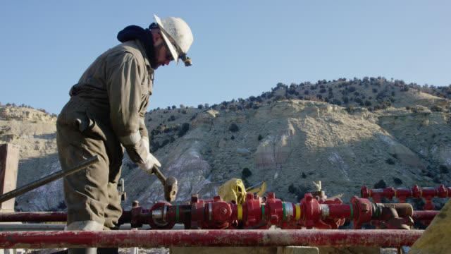 vídeos de stock, filmes e b-roll de tiro em câmera lenta de um trabalhador de campo de petróleo em seus trinta anos bombeando linhas para baixo e batendo um tubo com um martelo em um local de perfuração de óleo e gás em uma manhã fria, ensolarada, de inverno - capacete equipamento
