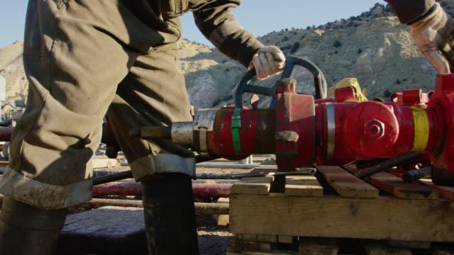 vídeos y material grabado en eventos de stock de disparo a cámara lenta de un trabajador de campos petrolíferos en sus trillas bombeando líneas y golpeando una tubería con un martillo en un sitio de almohadillas de perforación de petróleo y gas en una mañana fría, soleada e invernal - casco protector