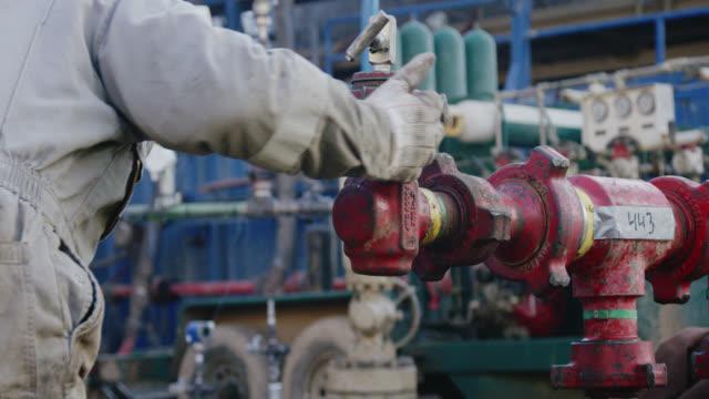 vidéos et rushes de tir au ralenti d'un travailleur de champ pétrolifère utilisant un marteau et pompant vers le bas des lignes à un site de plate-forme de forage de pétrole et de gaz sur un froid, matin d'hiver - latin american and hispanic ethnicity