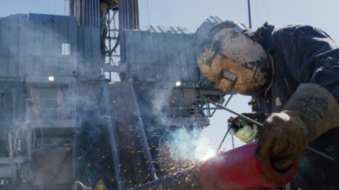 vídeos y material grabado en eventos de stock de disparo a cámara lenta de un trabajador de oilfield soldando dos tuberías juntas mientras las chispas vuelan junto a un derrick en un sitio de almohadillas de perforación de petróleo y gas en un día soleado - típico de la clase trabajadora
