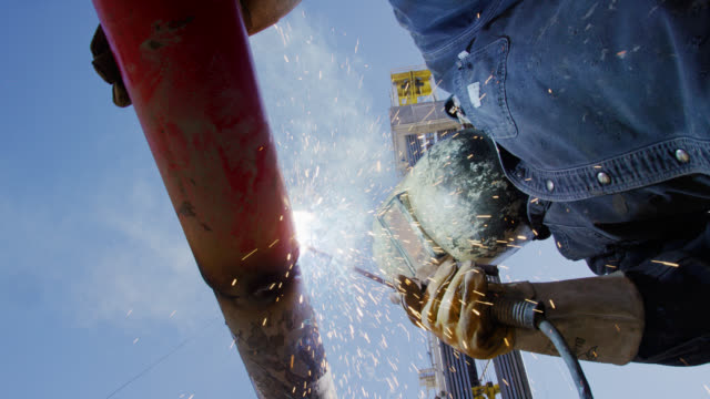 slow motion shot of an oilfield worker welding two pipes together as sparks fly next to a derrick at an oil and gas drilling pad site on a sunny day - oil industry stock videos & royalty-free footage