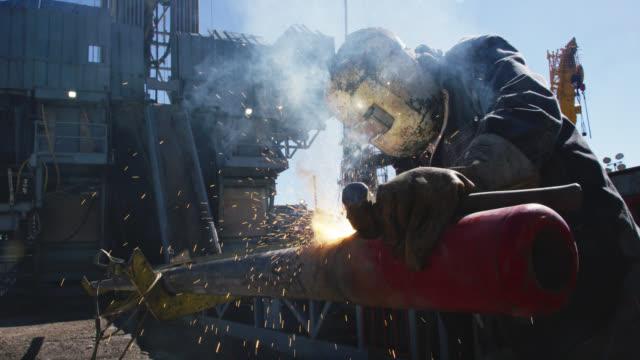 vidéos et rushes de slow motion shot d'un travailleur de champ pétrolifère soudant deux tuyaux ensemble pendant que les étincelles volent à côté d'un derrick à un site de plate-forme de forage de pétrole et de gaz sur une journée ensoleillée - sûreté