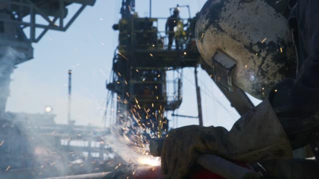 vídeos y material grabado en eventos de stock de disparo a cámara lenta de un trabajador de oilfield soldando dos tuberías juntas mientras las chispas vuelan junto a un derrick en un sitio de almohadillas de perforación de petróleo y gas en un día soleado - soldador