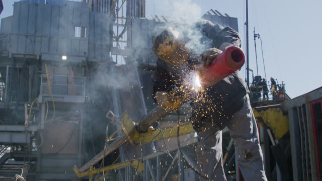 slow motion shot of an oilfield worker welding two pipes together as sparks fly next to a derrick at an oil and gas drilling pad site on a sunny day - gefahr stock-videos und b-roll-filmmaterial