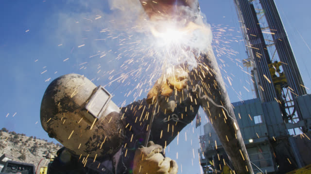 slow motion shot of an oilfield worker welding two pipes together as sparks fly next to a derrick at an oil and gas drilling pad site on a sunny day - occupazione industriale video stock e b–roll