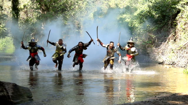 slow motion shot of ancient warriors running and shouting to fight with enemy at the river - ancient stock videos & royalty-free footage