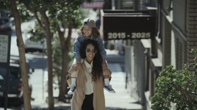 slow motion shot of approaching woman carrying daughter on shoulders uphill in city / san francisco, california, united states - baseballmütze stock-videos und b-roll-filmmaterial