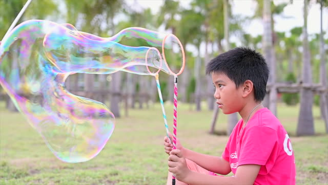 slow motion shot of asian happy little kid blowing and playing soap of bubble wand in garden - bubble wand stock videos & royalty-free footage