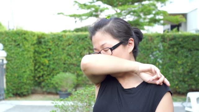vídeos de stock e filmes b-roll de slow motion shot of asian women coughing into elbow at the garden. - elbow