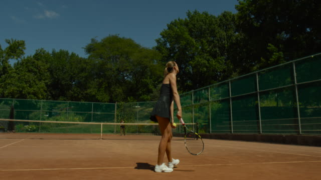 slow motion shot of back of woman serving tennis ball to opponent on clay court - forehand stock videos & royalty-free footage