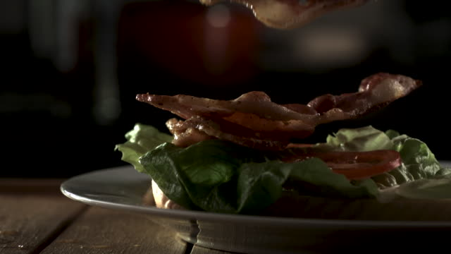slow motion shot of bacon falling onto a sandwich. - sandwich stock videos & royalty-free footage