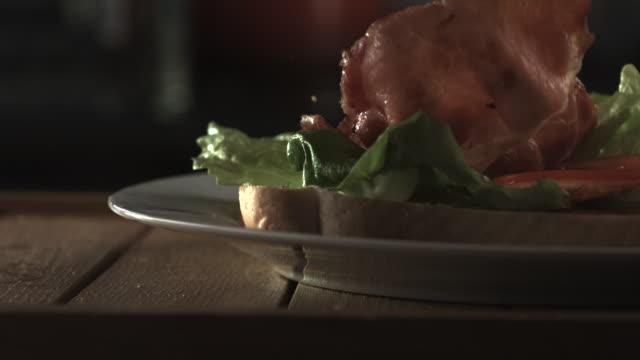 Slow motion shot of bacon falling onto a sandwich.