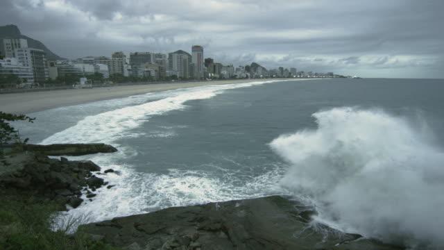 vídeos de stock, filmes e b-roll de slow motion shot of big waves crashing onto the rocks at the beach in rio de janeiro, brazil - fotografia de alta velocidade