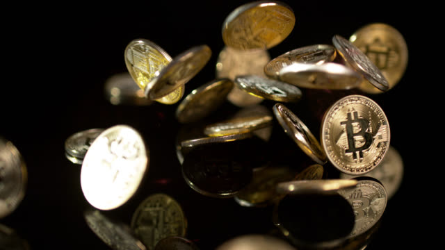 Slow motion shot of Bitcoins falling onto a reflective surface.