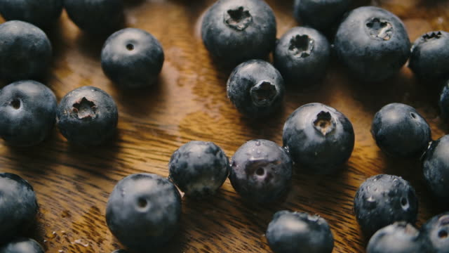 slow motion shot of blueberries grapes falling on the wood table background studio shot - blueberry stock videos & royalty-free footage
