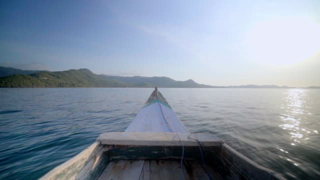 slow motion shot of boat moving towards mountains while sailing on sea against bright sky, wooden nautical vessel on water during sunny day - lombok, bali - nautical vessel点の映像素材/bロール