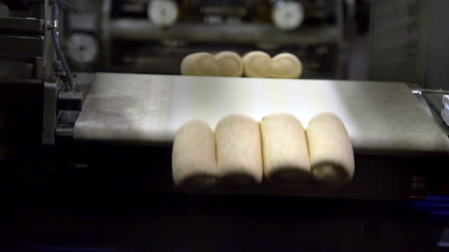 slow motion shot of bread dough falling off a conveyor belt and into bread tins - pane video stock e b–roll