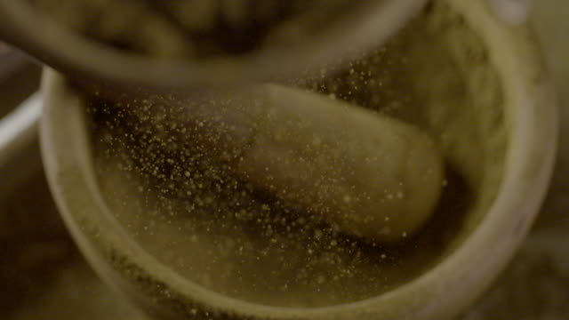 Slow motion shot of brown ochre being sieved over a mortar and pestle.