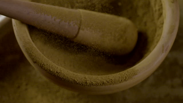 Slow motion shot of brown ochre being sifted through a sieve over a mortar and pestle.