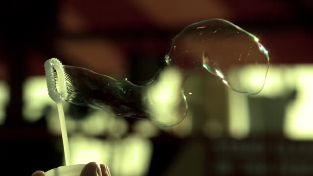 Slow motion shot of bubbles being blown from a bubble wand.