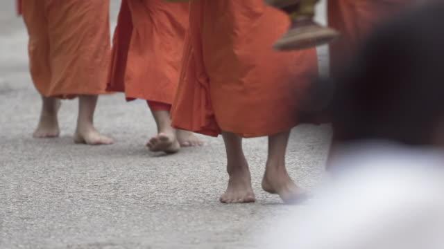 slow motion shot of buddhist monks wearing saffron robes while walking barefoot on street in city - luang prabang, laos - 僧点の映像素材/bロール