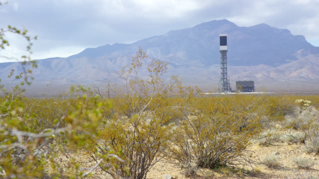 slow motion shot of bushes blow in the wind with the ivanpah solar power facility at the base of clark mountain and storm clouds overhead in the mojave desert in california - arid stock videos & royalty-free footage