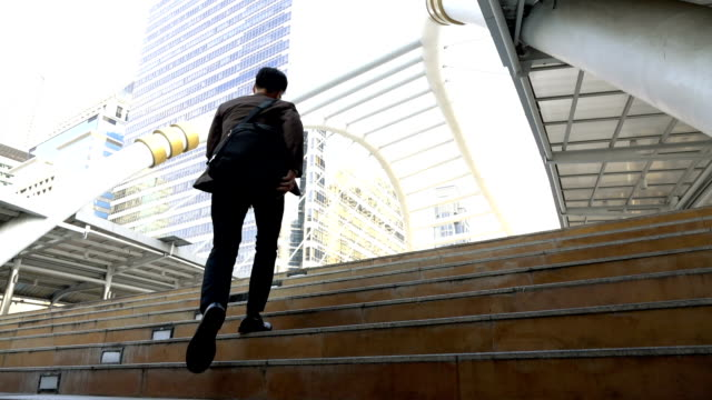 Slow motion shot of business man rushing up stairs to work in modern city