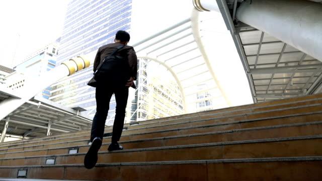 Al rallentatore di un uomo d'affari di correre su scale di lavorare in città moderna