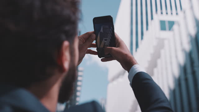 slow motion shot of businessman taking pictures with smartphone - photographing stock videos & royalty-free footage
