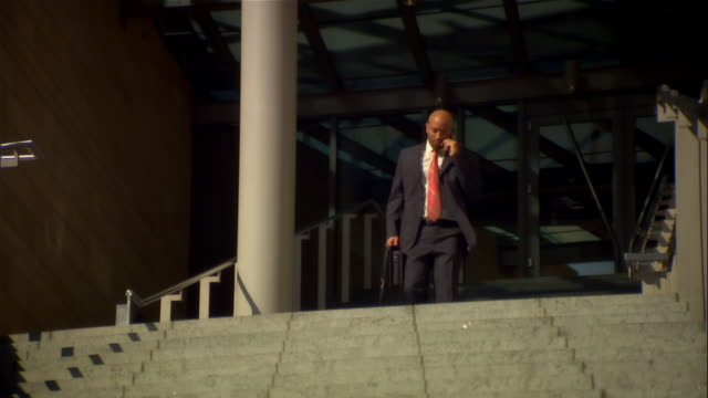 vídeos de stock, filmes e b-roll de slow motion shot of businessman talking on cell phone while walking down stairs outside building / getting off phone - neckwear