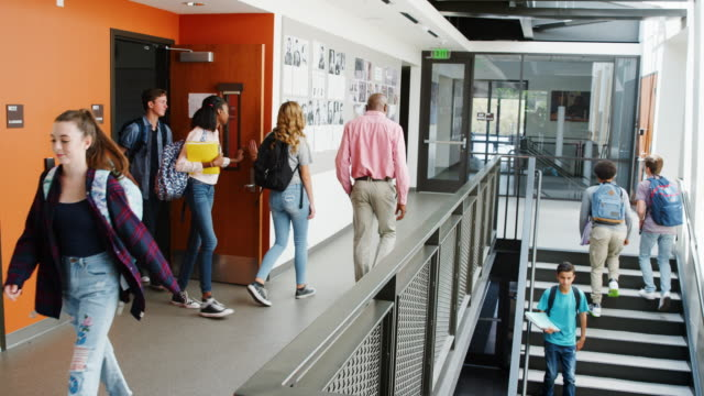 Slow-Motion Shot van drukke Middelbare School Corridor tijdens reces met studenten en medewerkers