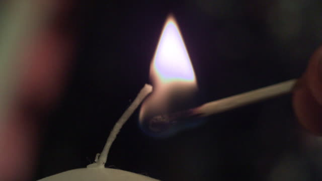 slow motion shot of candle being lit by a match. - candle stock videos and b-roll footage
