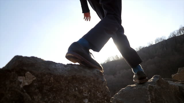 vídeos de stock e filmes b-roll de slow motion shot of carefree man balancing on stones at the shore. nature with trees in the background. symbolizing ideas, overcoming obstacles, creativity. - water's edge