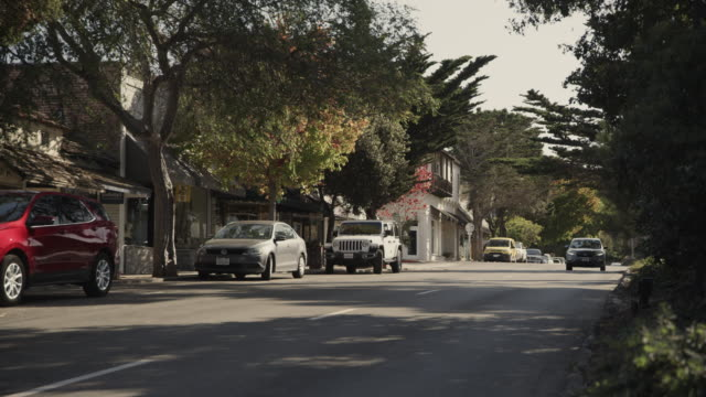 slow motion shot of cars driving on quiet city street / carmel, california, united states - carmel california stock videos & royalty-free footage