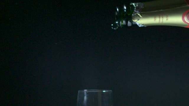 Slow motion shot of champagne being poured into a glass.