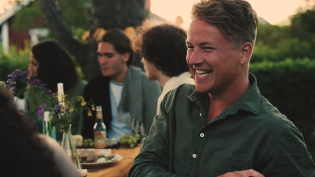 Slow motion shot of cheerful man talking while sitting with friends in backyard