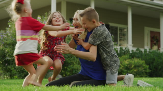 slow motion shot of children surprising mother sitting on lawn then falling on her / pleasant grove, utah, united states - vier personen stock-videos und b-roll-filmmaterial
