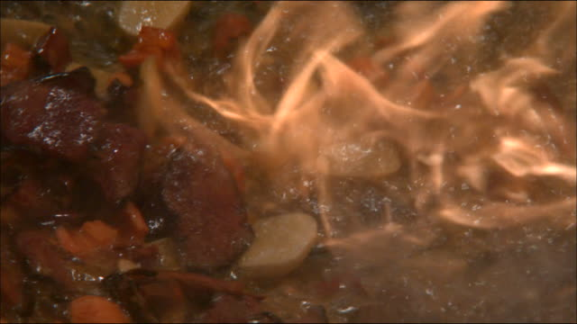 vídeos de stock e filmes b-roll de slow motion shot of chinese food being cooked on a wok with fire - comida chinesa
