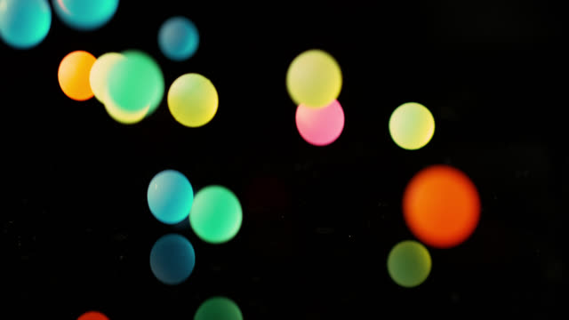 slow motion shot of colourful balls falling onto a mirrored surface. - ball stock videos & royalty-free footage