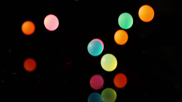 vídeos de stock e filmes b-roll de slow motion shot of colourful balls falling onto a mirrored surface. - esfera