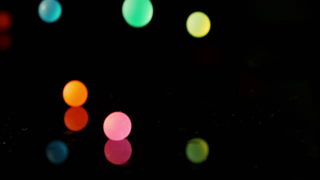 Slow motion shot of colourful balls falling onto a mirrored surface.