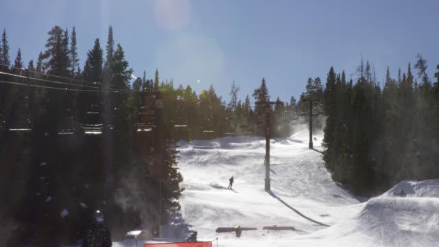 スキーヤーが明るく晴れた晴れた日にコロラド州ボルダー近くのエルドラスキーリゾートで森に囲まれたスキーリフトの下でスキーランを滑り降りるように空中に浮かぶ凝縮のスローモーシ� - ゲレンデ点の映像素材/bロール