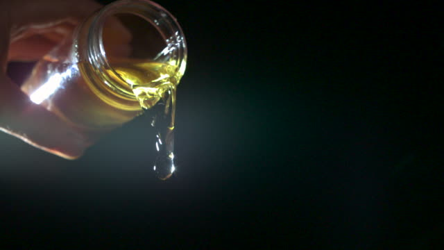 Slow motion shot of cooking oil being poured out of a glass jar.