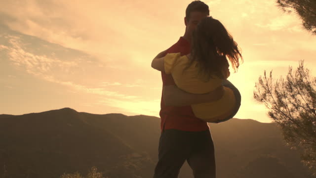 slow motion shot of couple dancing and twirling overlooking mountain. - lift stock videos & royalty-free footage
