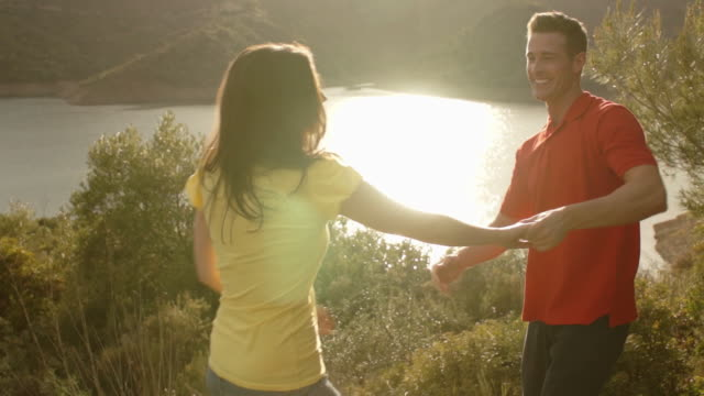 slow motion shot of couple dancing by lake. - slow dancing stock videos and b-roll footage